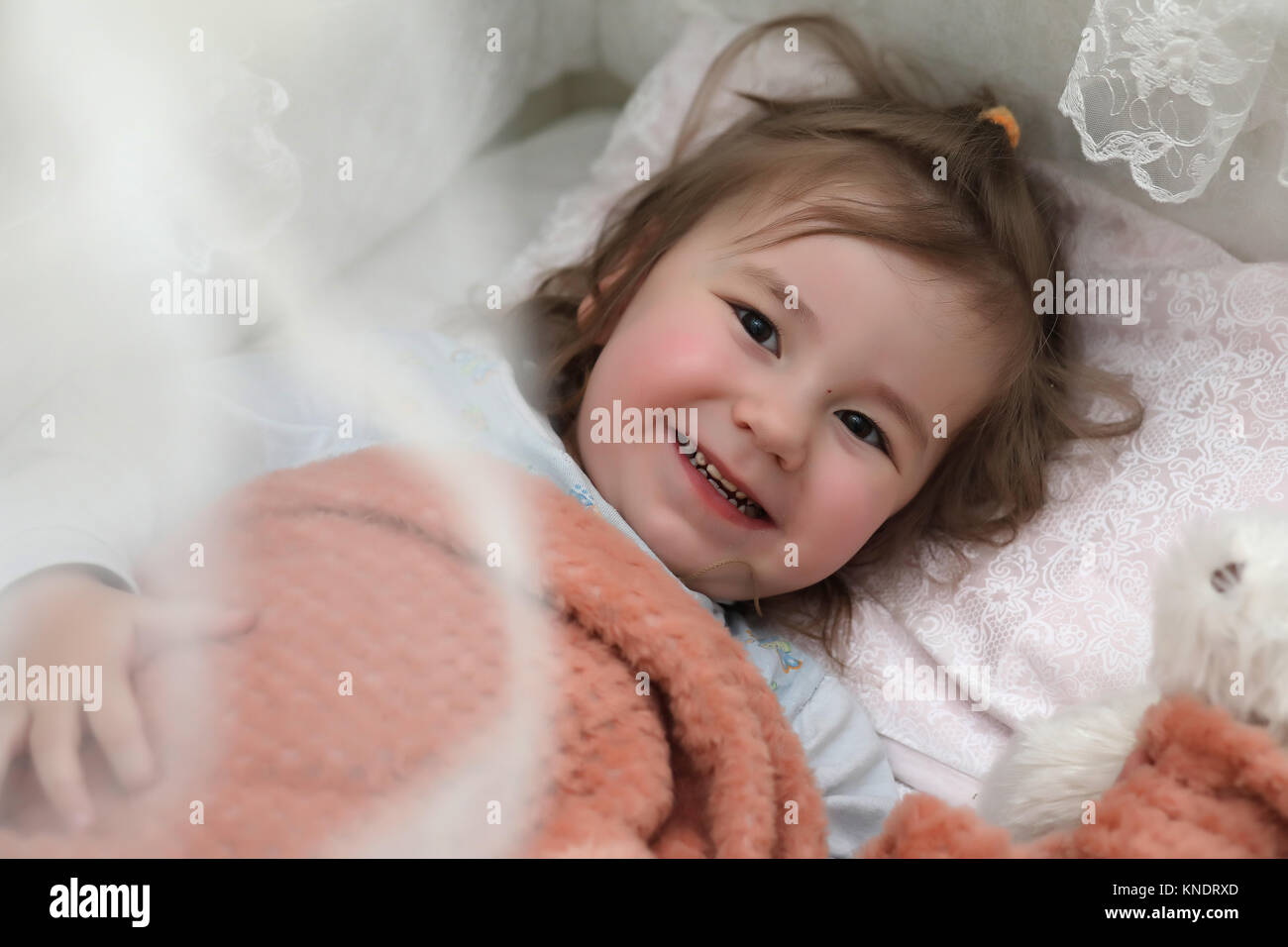 Little girl lies in bed on pillow - Stock Image