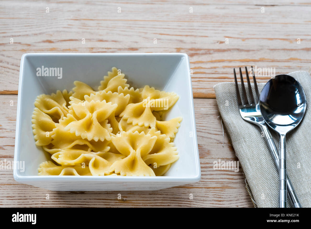 Bowl cooked farfalle pasta with fork and spoon and napkin, serviette. - Stock Image