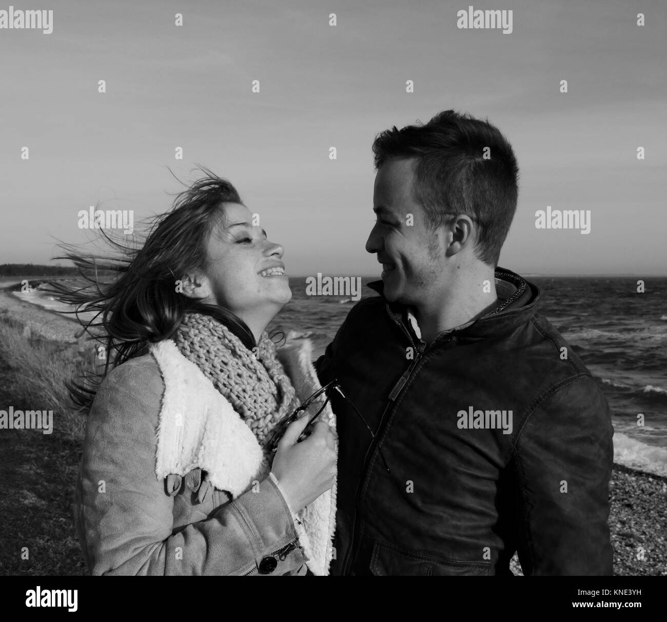 Black and white close up of attractive young couple on the beach on a windy winter's day looking into each others - Stock Image