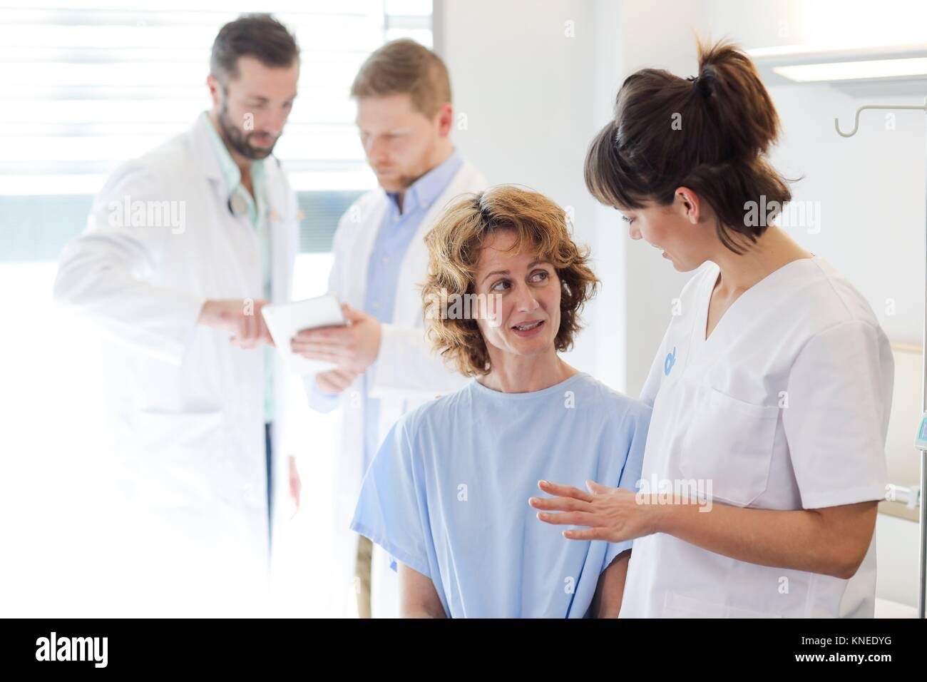 Patient in hospital room attended by a doctor, Hospital - Stock Image