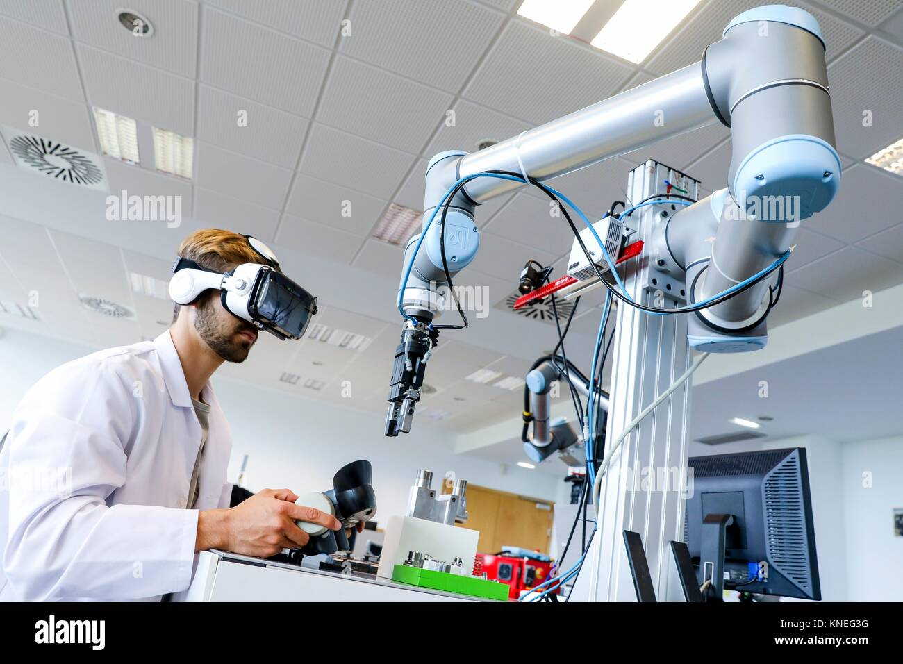 Researcher with virtual reality glasses, VR, Humanoid robot for automotive assembly tasks in collaboration with - Stock Image