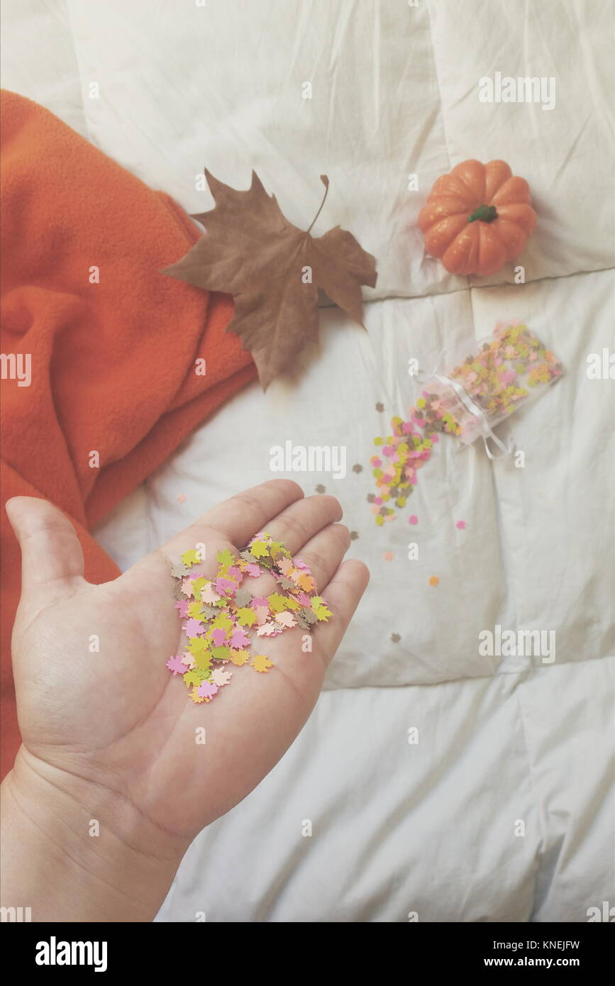 Woman's hand holding confetti and autumn decorations - Stock Image