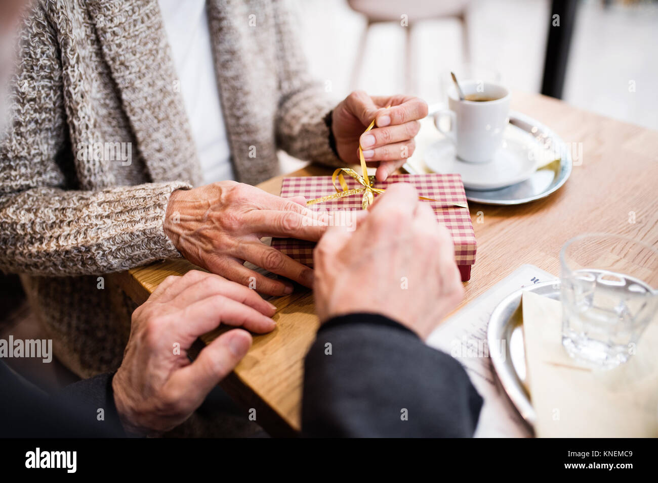 Senior couple with a present in a cafe. Christmas time. - Stock Image