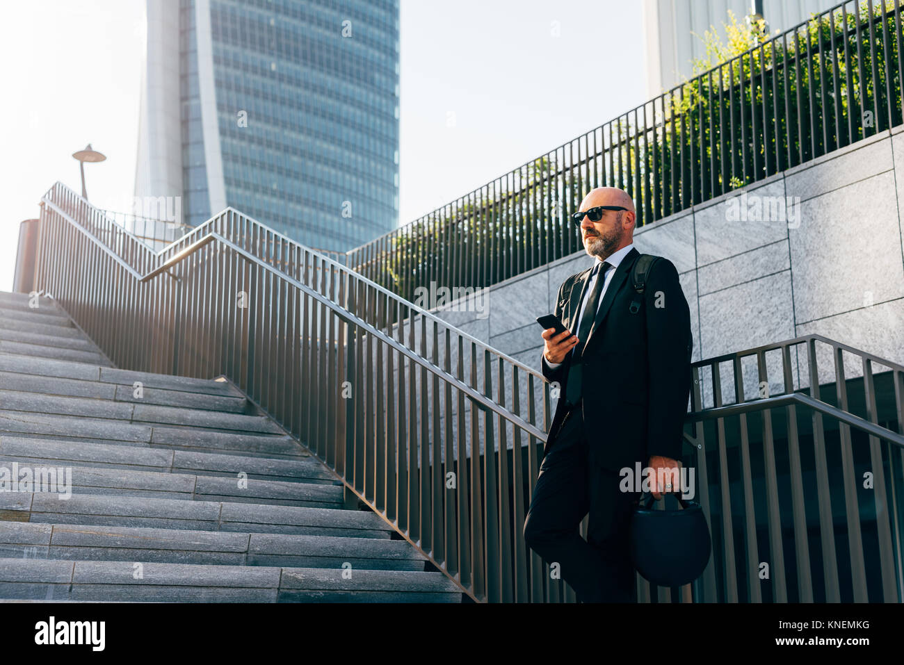 Mature businessman standing on steps, using smartphone, low angle view Stock Photo