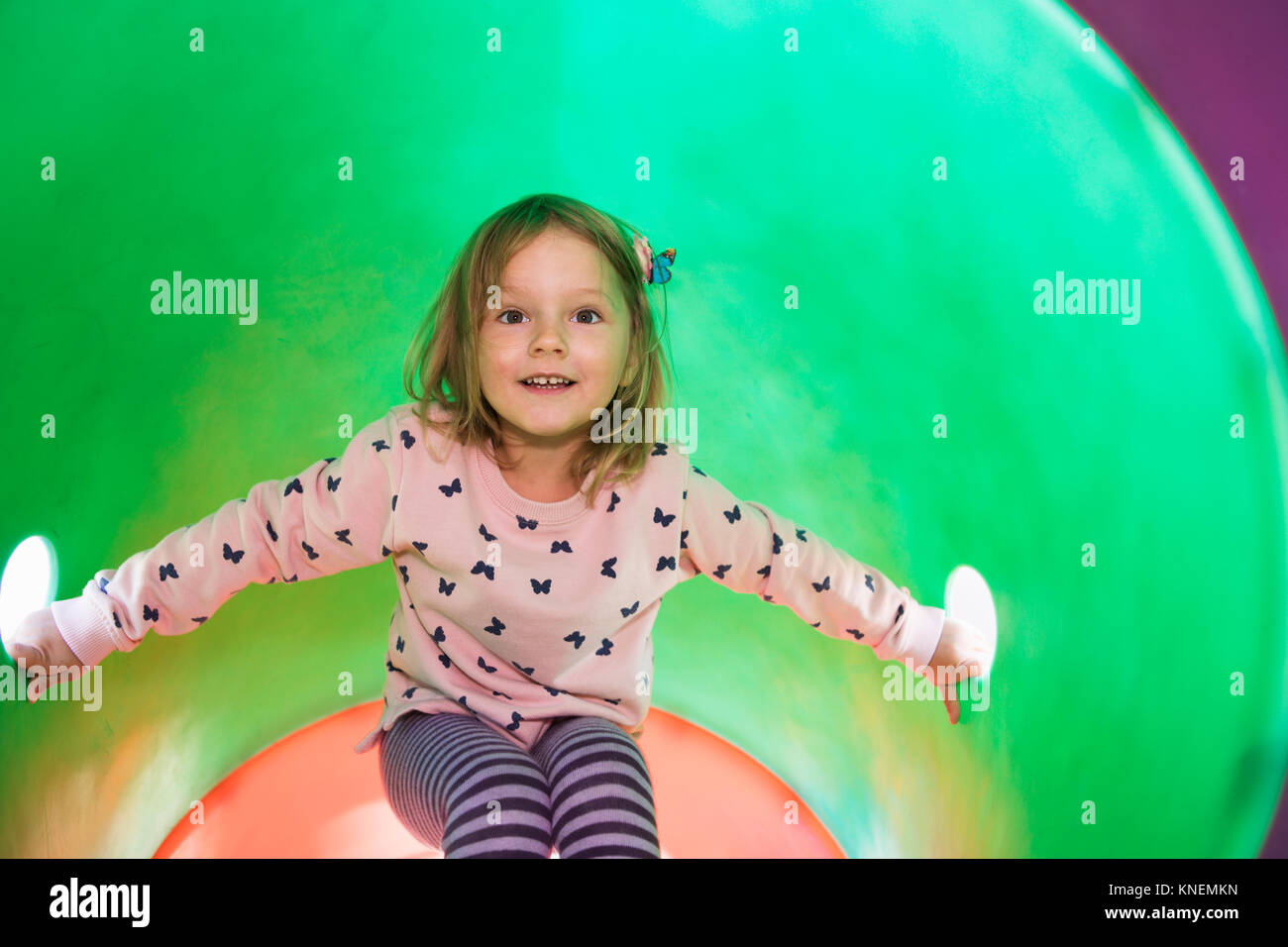 Girl in tube on climbing frame looking at camera smiling - Stock Image