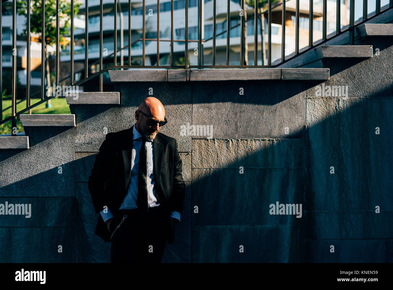 Portrait of mature businessman outdoors, standing beside steps, pensive expression Stock Photo