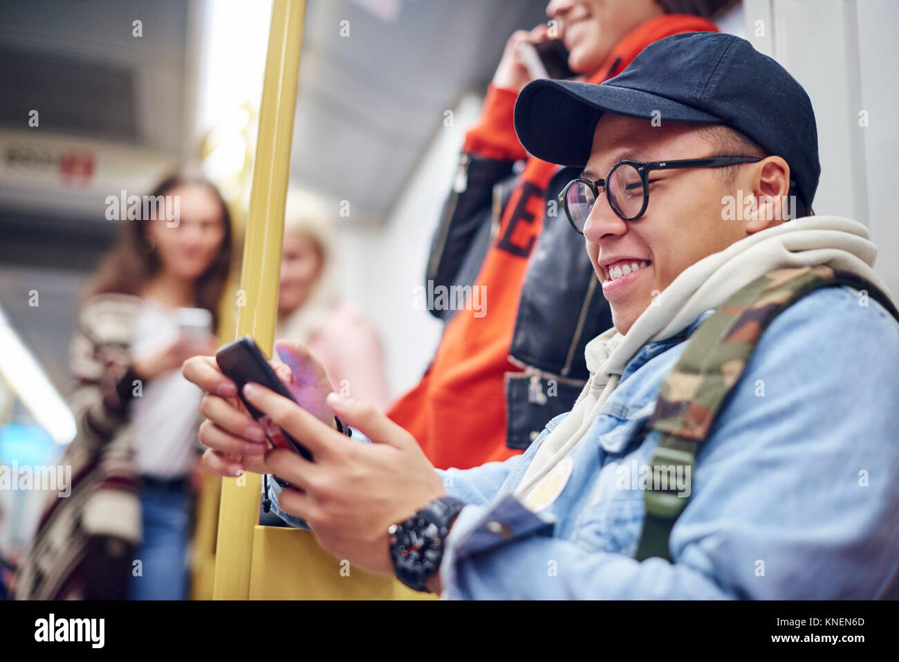 Young man looking at smartphone on city tram - Stock Image