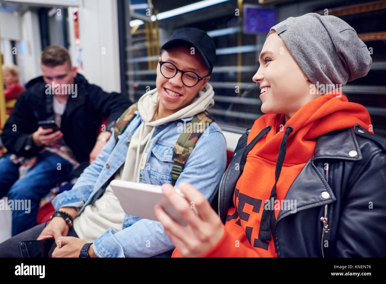 Young couple waiting in underground station looking at smartphone - Stock Image
