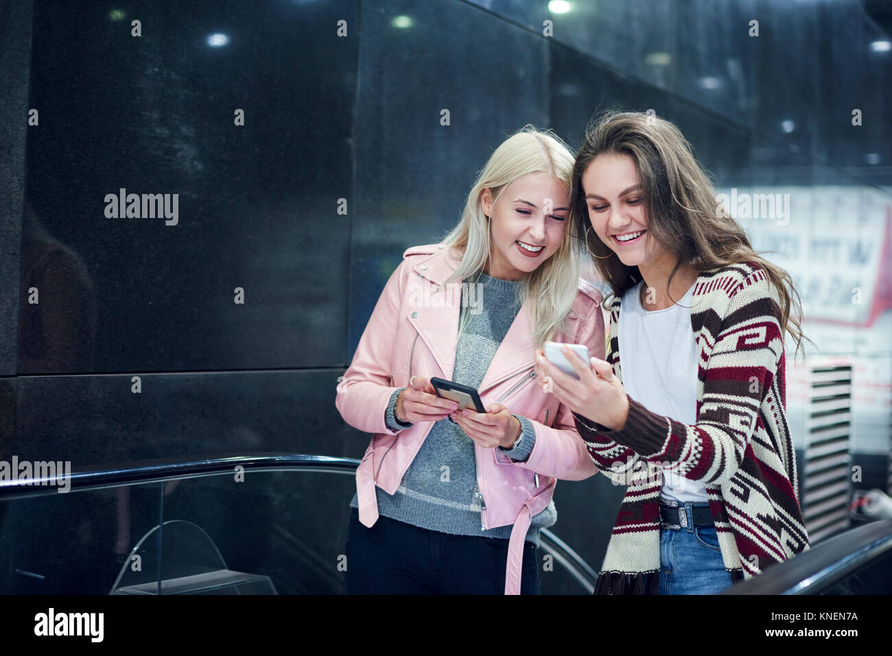 Two young women moving up underground station escalator  looking at smartphone - Stock Image