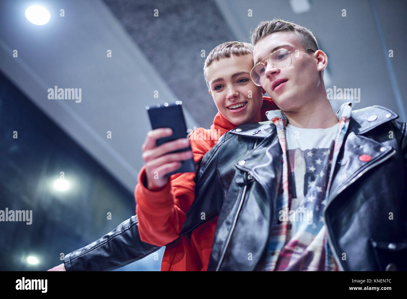 Young couple moving down underground station escalator  looking at smartphone - Stock Image