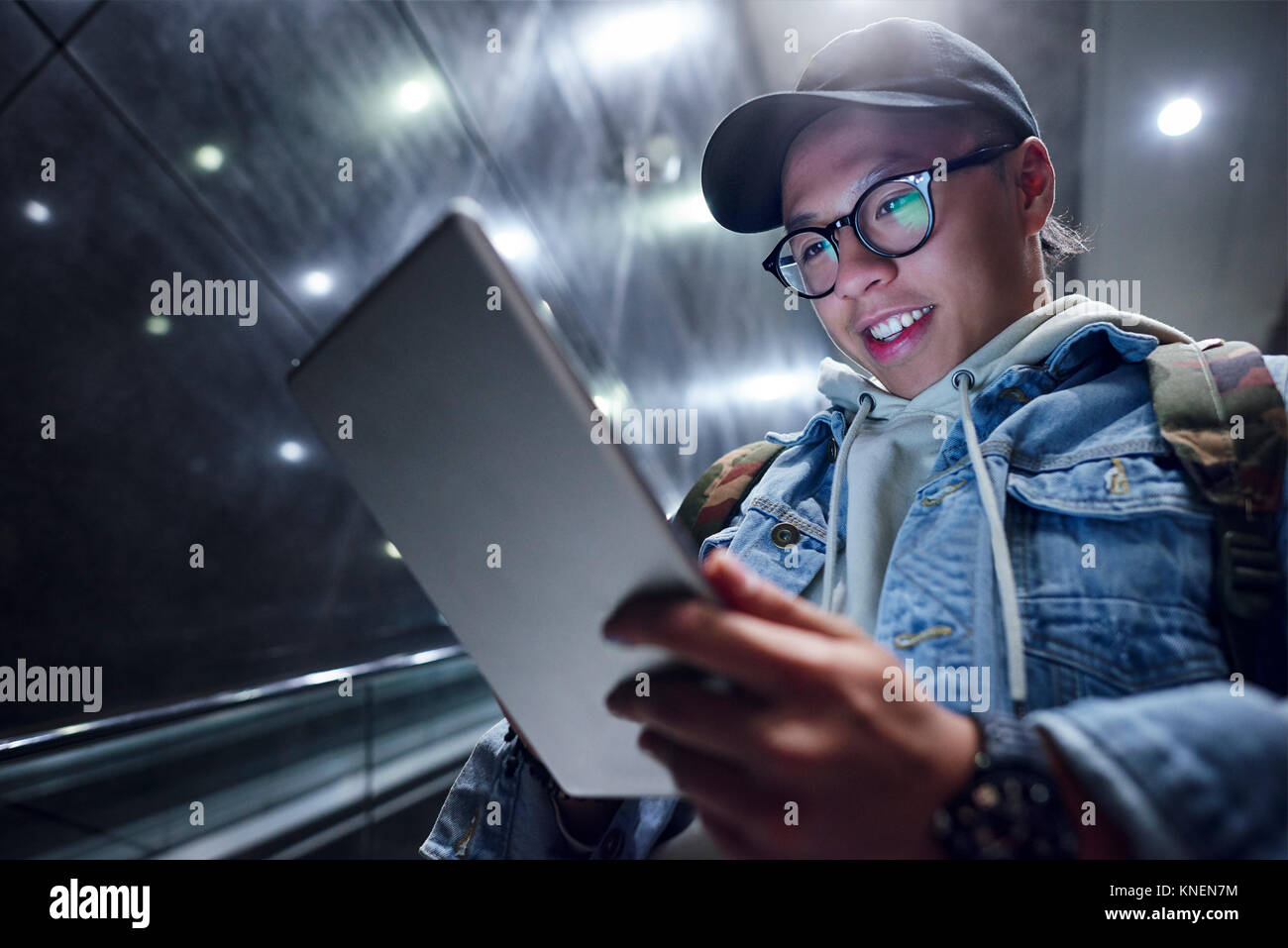 Young man moving down underground station escalator  looking at digital tablet - Stock Image