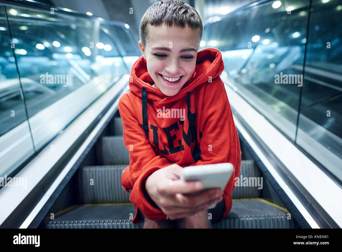 Short haired young woman moving down underground station escalator  looking at smartphone - Stock Image