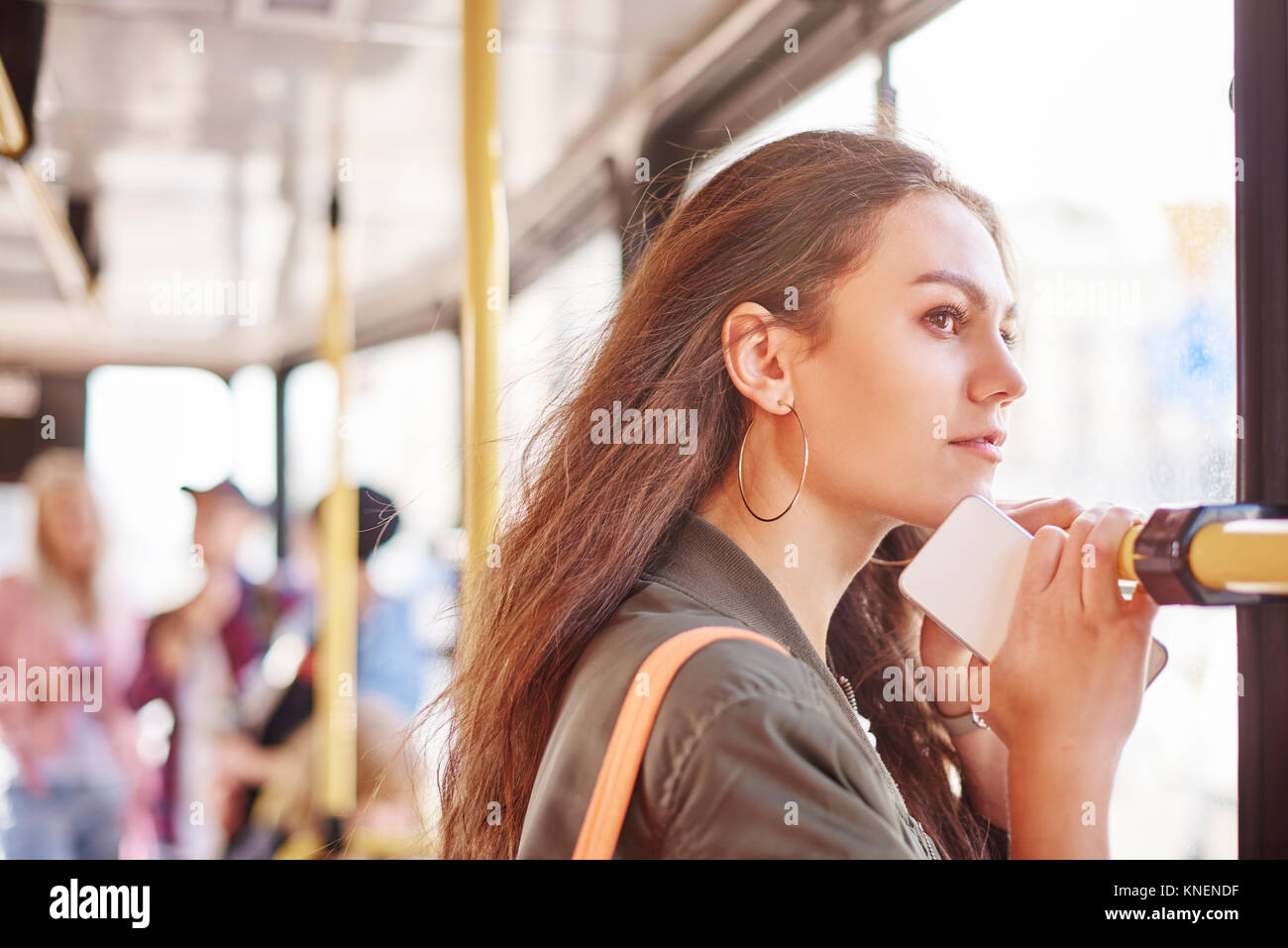 Young woman on city tram gazing out through window - Stock Image
