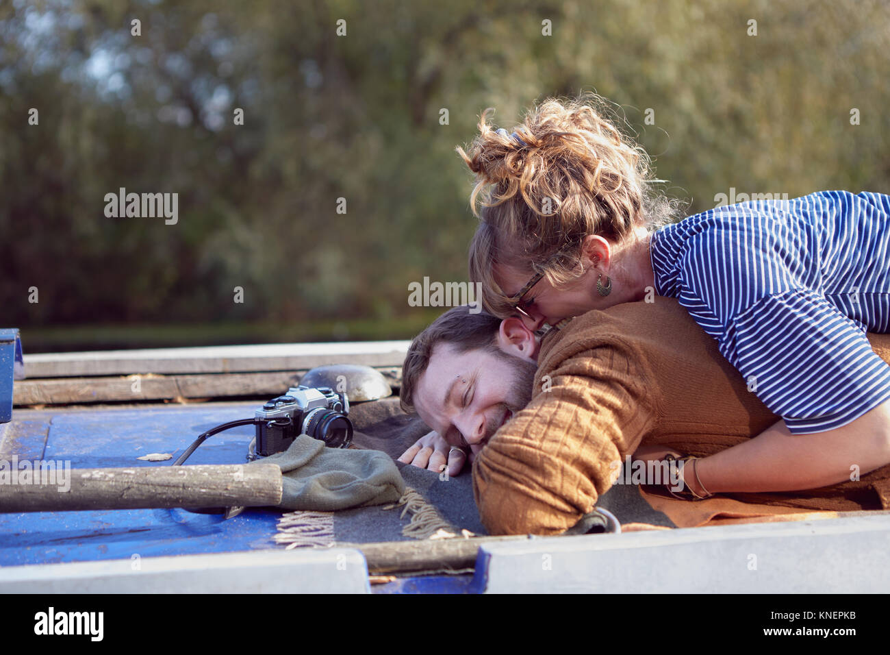 Couple lying on roof of canal boat - Stock Image