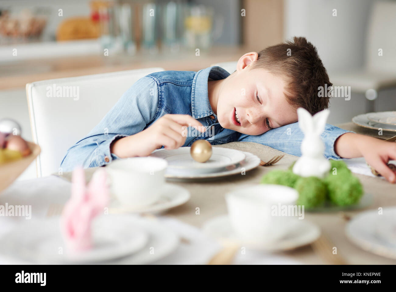 Boy at dining table playing with golden easter egg on plate - Stock Image