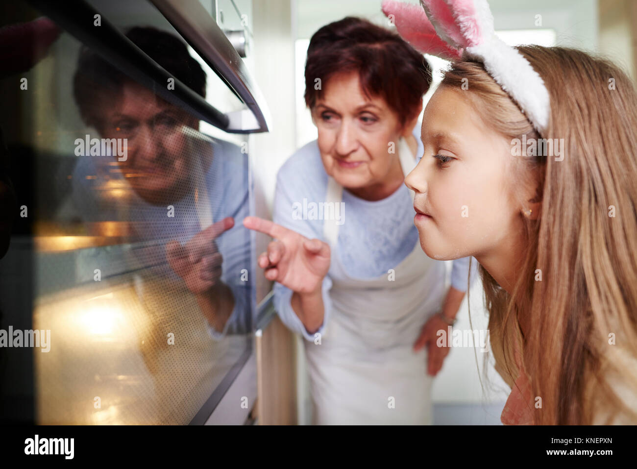 Girl and grandmother watching easter biscuits in kitchen oven - Stock Image