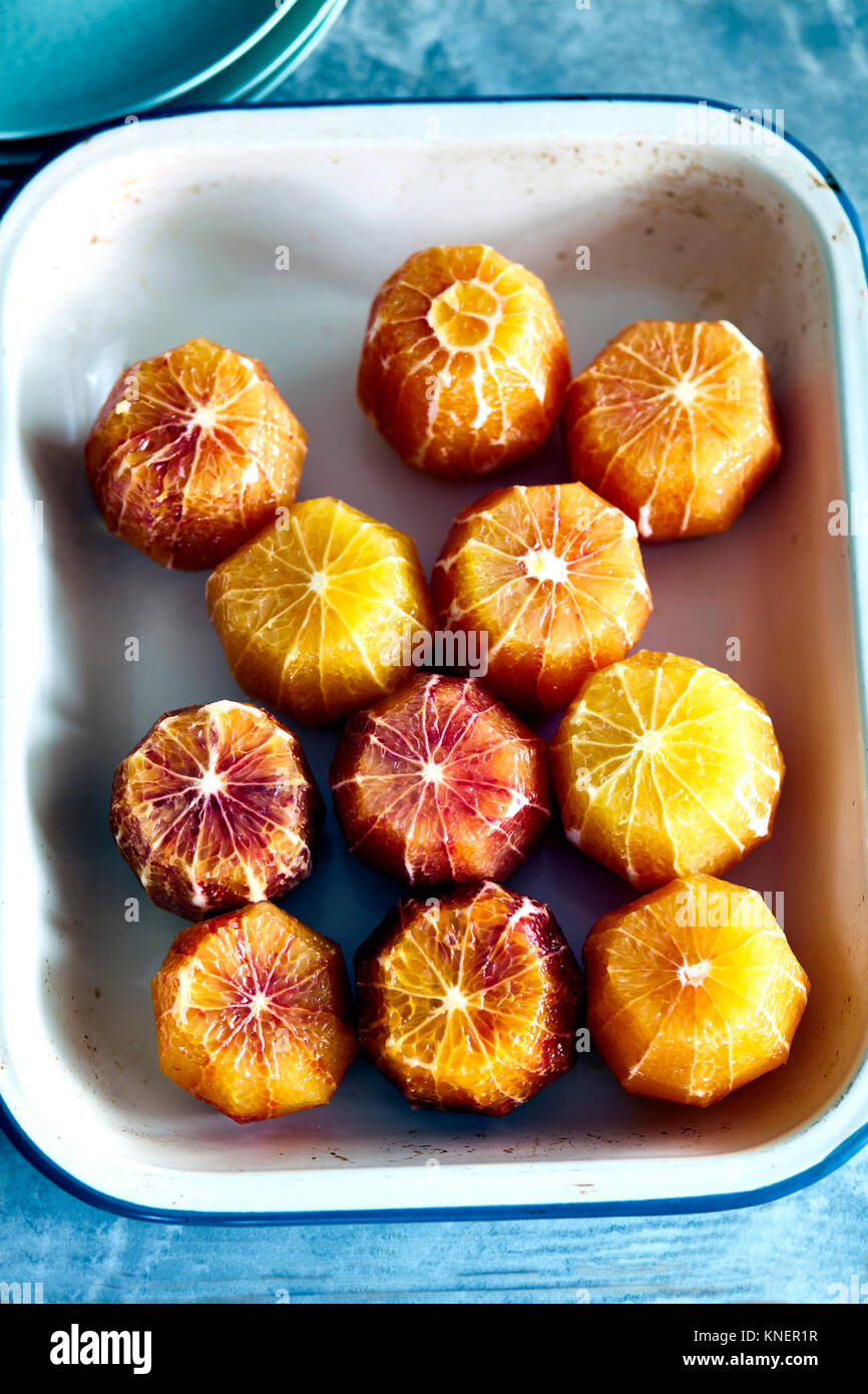 Peeled blood oranges in baking tray, elevated view - Stock Image