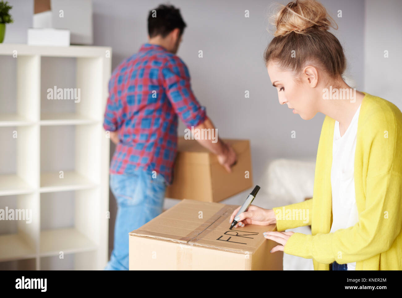 Young couple moving home, young woman labelling cardboard box - Stock Image