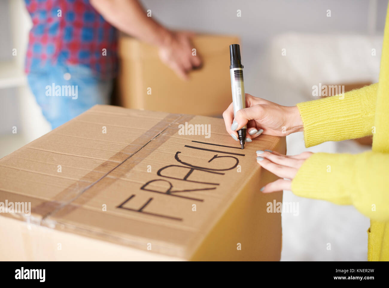 Young couple moving home, young woman labelling  cardboard box, mid section - Stock Image