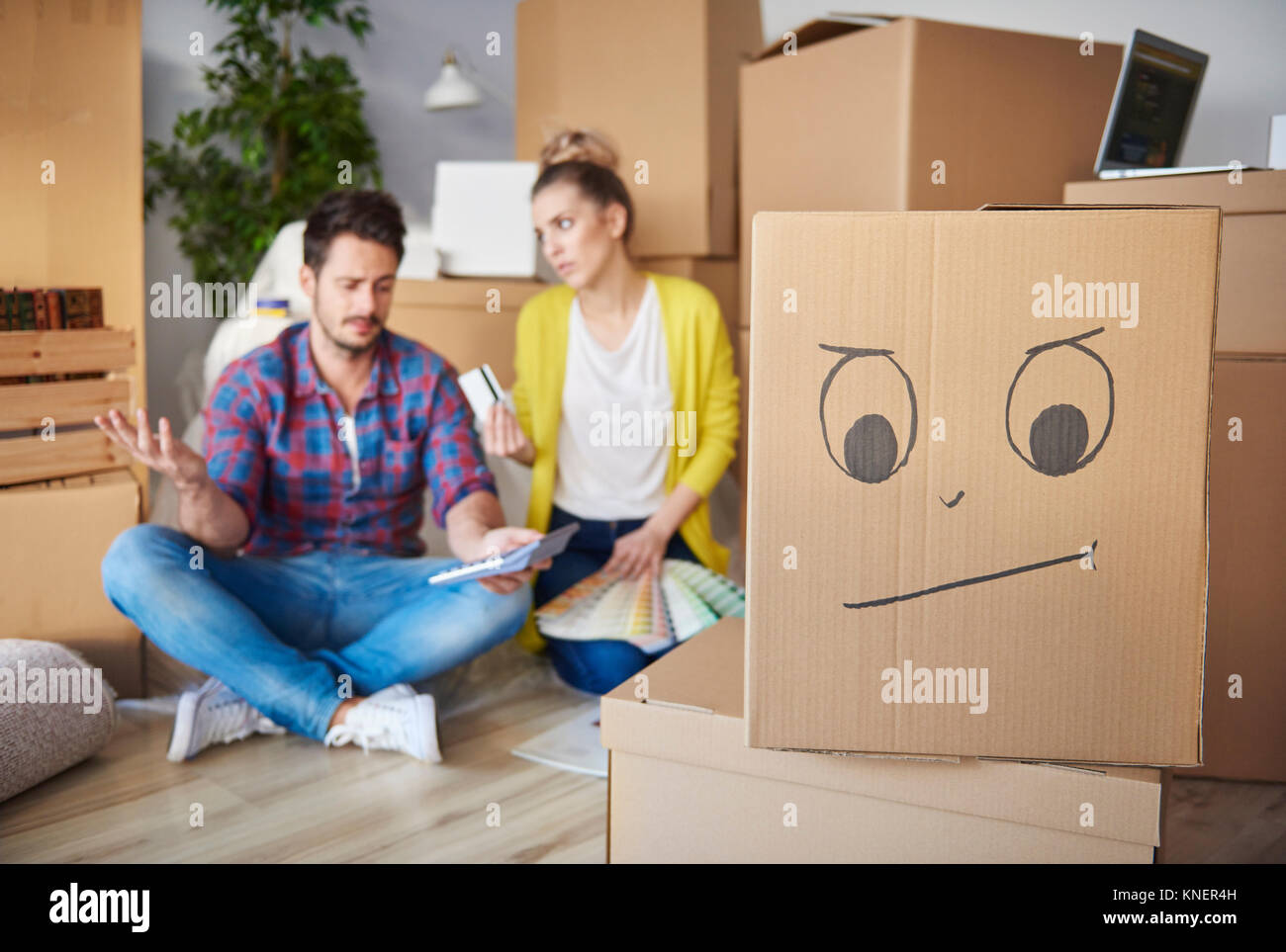 Young couple at home, surrounded by cardboard boxes, working out finances - Stock Image