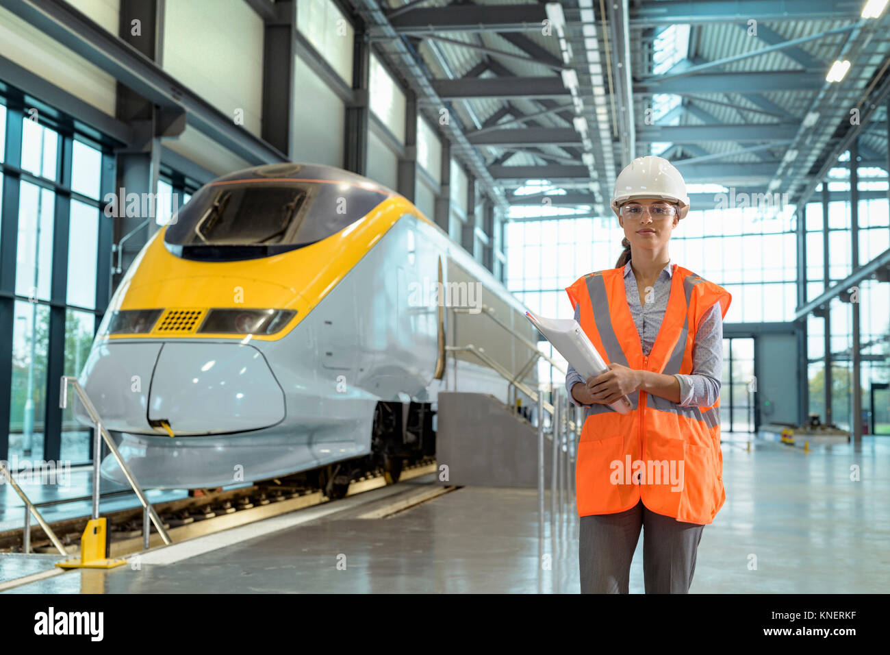 Portrait of female apprentice at railway engineering facility - Stock Image