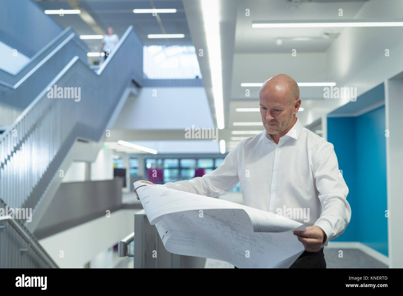 Engineer studying technical drawings in railway engineering facility - Stock Image