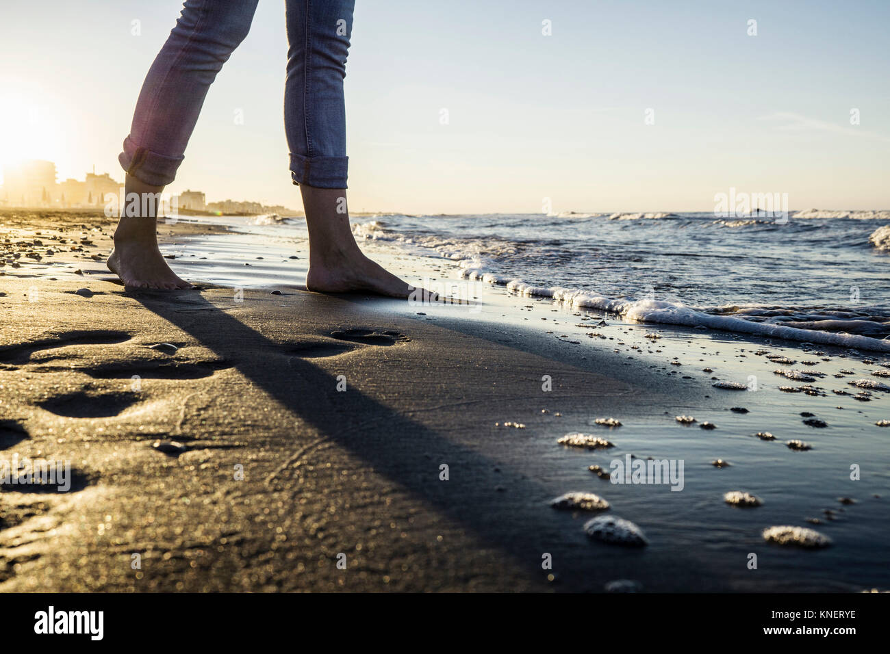 Legs of barefooted woman standing at water's edge on beach, Riccione, Emilia-Romagna, Italy - Stock Image