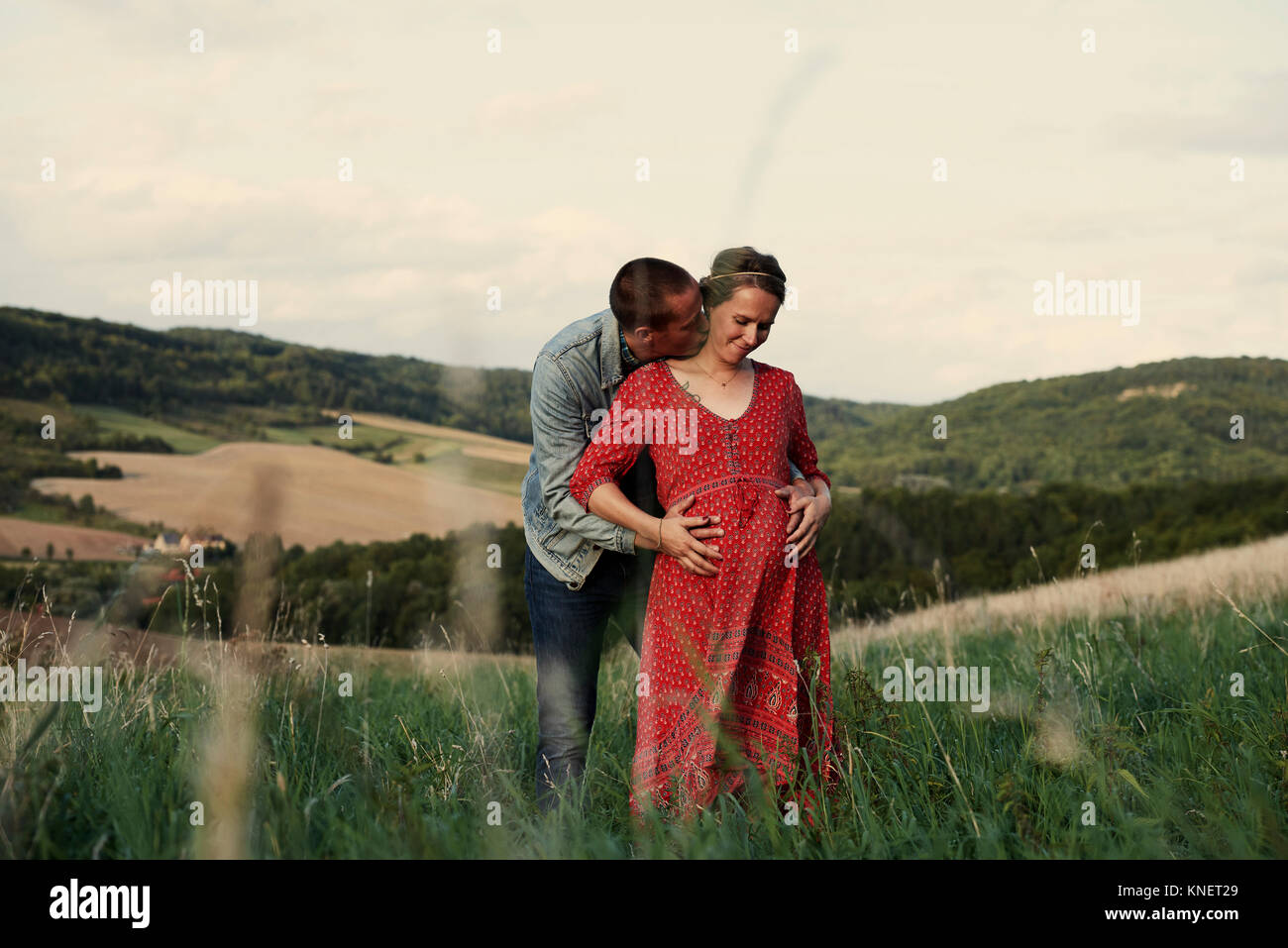 Romantic man with hands on pregnant wife's stomach in landscape - Stock Image