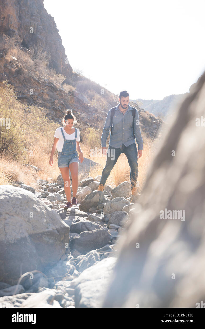 Young hiking couple hiking over rocks in valley, Las Palmas, Canary Islands, Spain - Stock Image