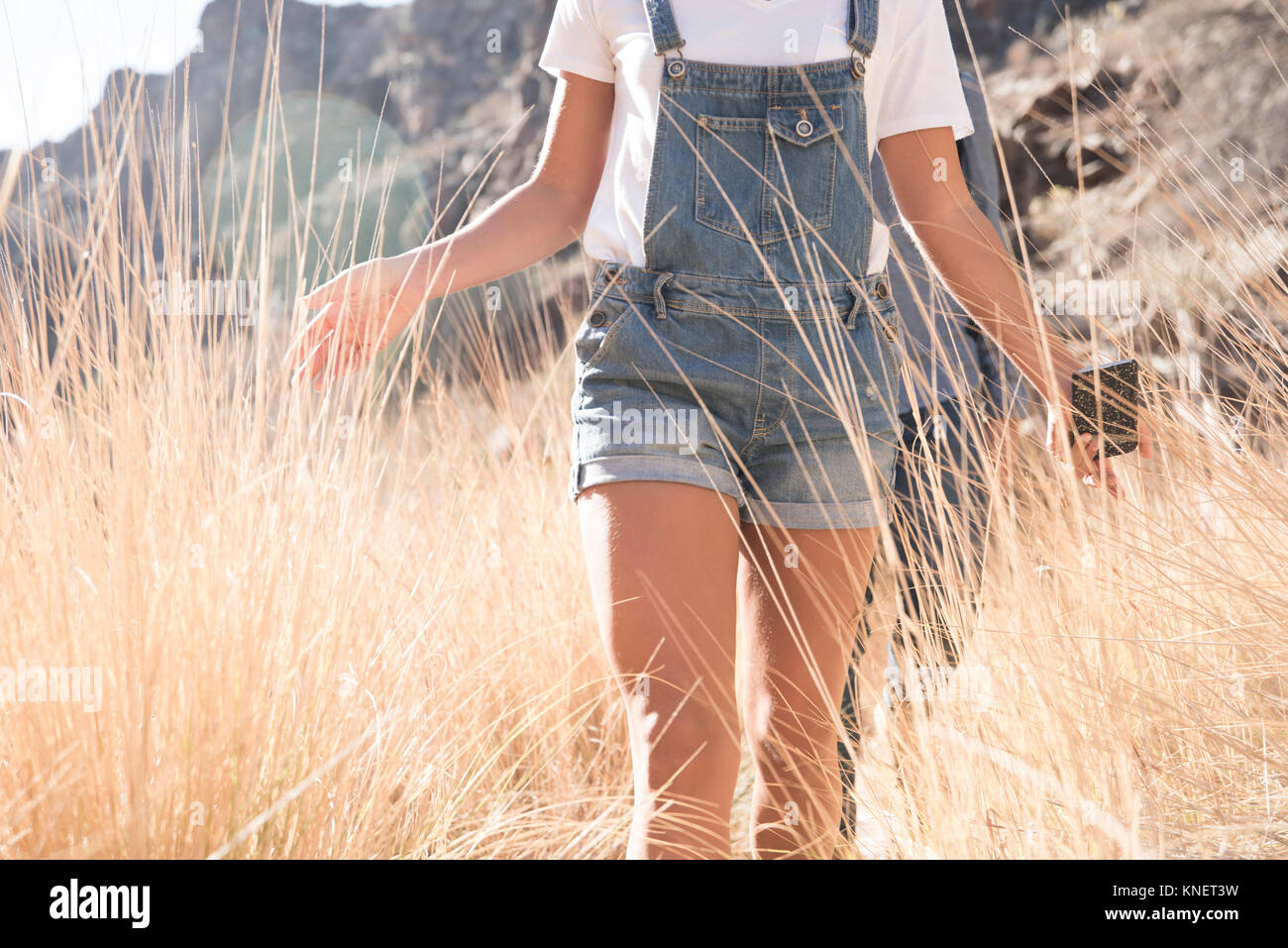 Mid section of young hiking couple touching long grass while hiking in valley, Las Palmas, Canary Islands, Spain - Stock Image