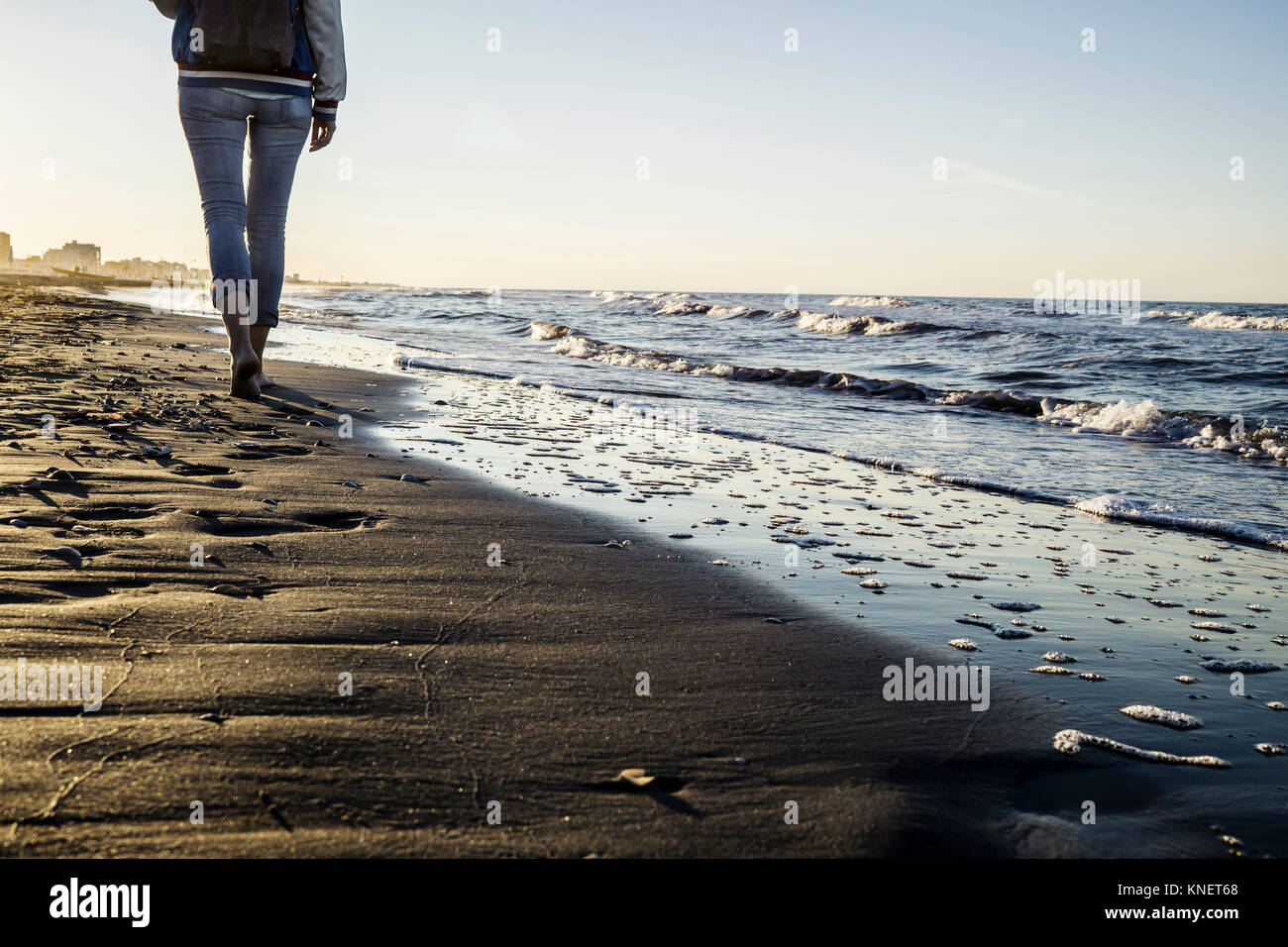 Waist down view of barefooted woman strolling along water's edge on beach, Riccione, Emilia-Romagna, Italy - Stock Image