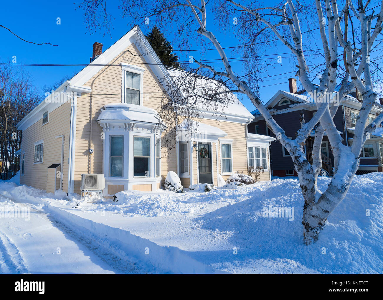 Older traditional house in wintertime in a North American neighborhood. - Stock Image