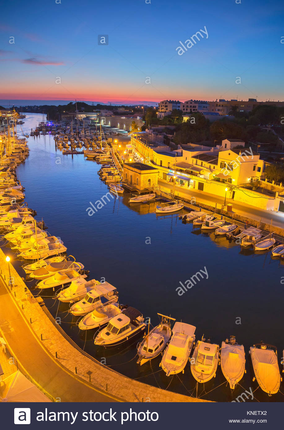 High angle view of historic harbour and rows of moored boats at dusk, Ciutadella, Menorca, Balearic Islands, Spain - Stock Image