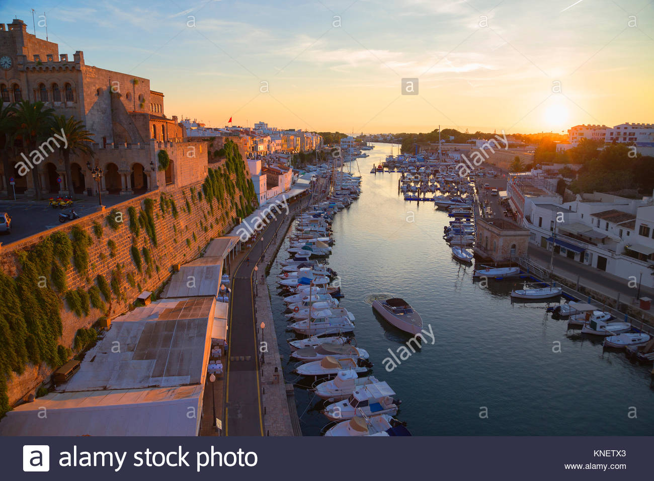 View of historic harbour waterfront and town hall at sunset, Ciutadella, Menorca, Balearic Islands, Spain - Stock Image