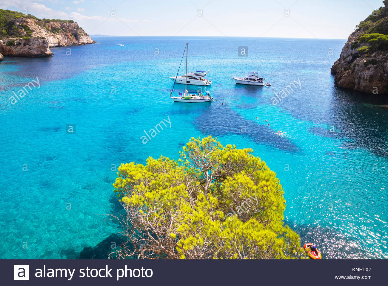 View of yachts anchored in blue sea at Cala Mitjana bay, Menorca, Balearic Islands, Spain - Stock Image
