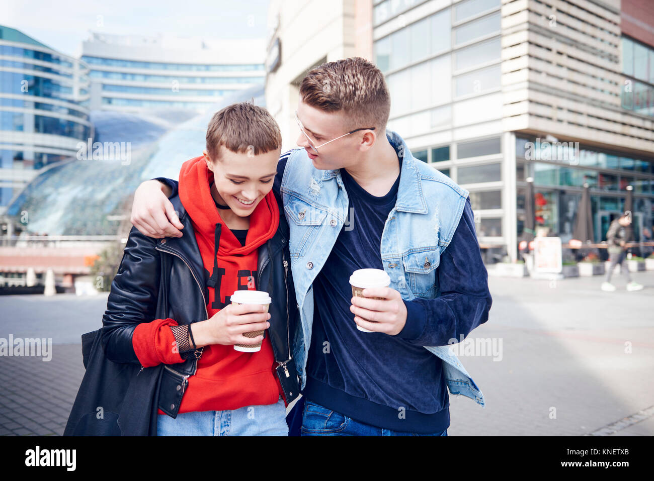 Romantic young couple with takeaway coffee walking together in city - Stock Image