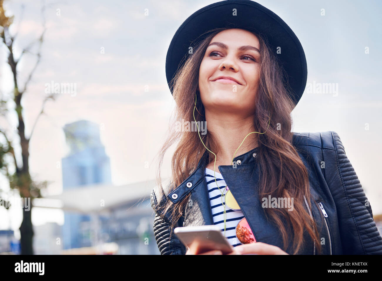 Portrait of young woman in trilby hat in city - Stock Image