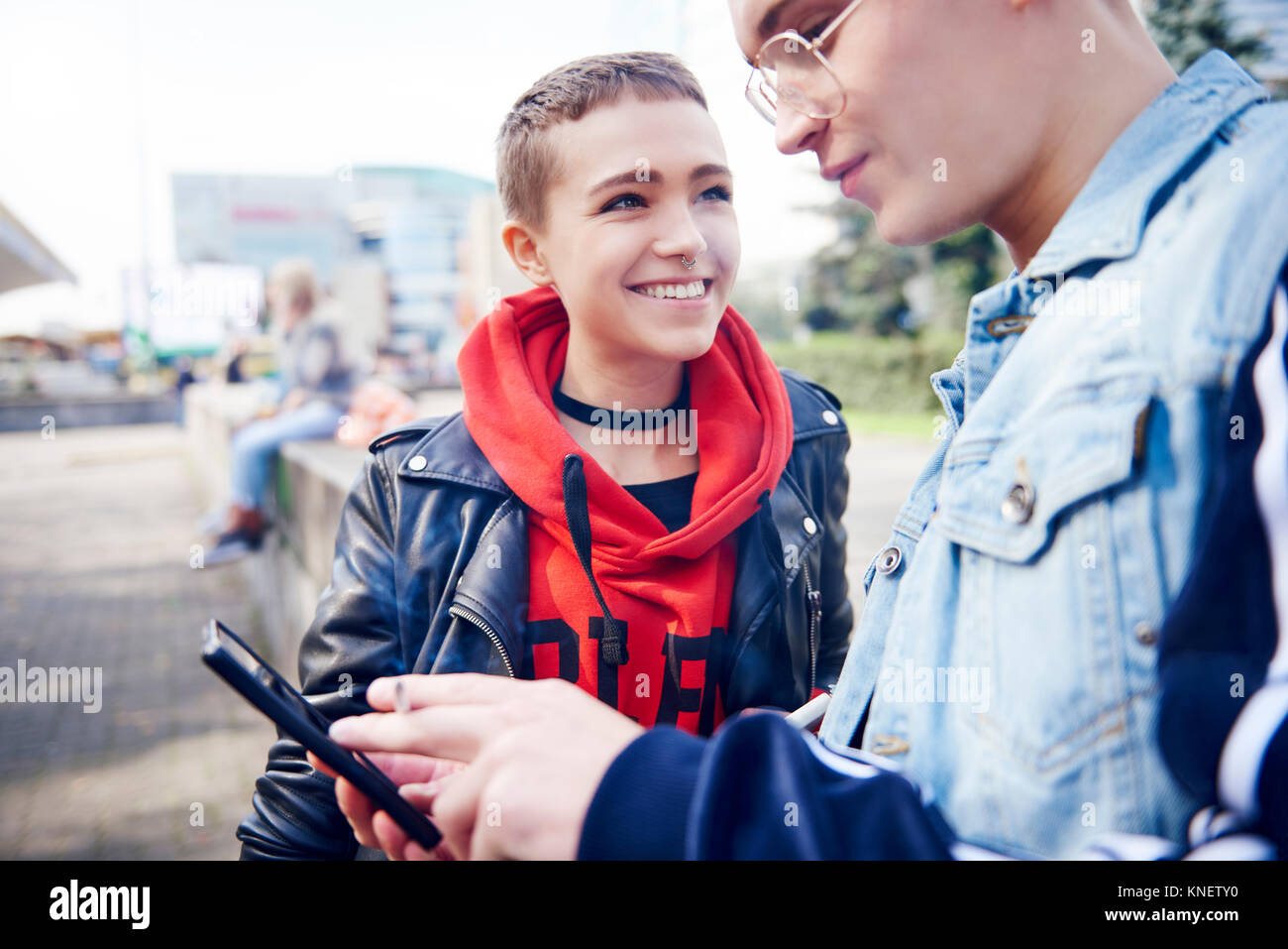 Young couple looking at smartphone in city - Stock Image