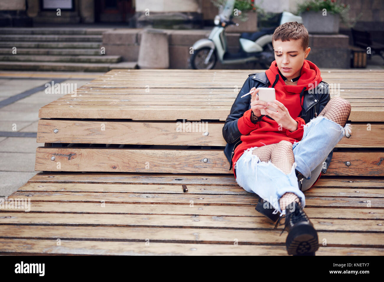 Cool young woman with short hair looking at smartphone and smoking cigarette on city bench - Stock Image
