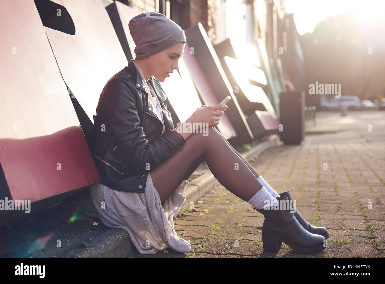 Cool young woman sitting on city street looking at smartphone - Stock Image