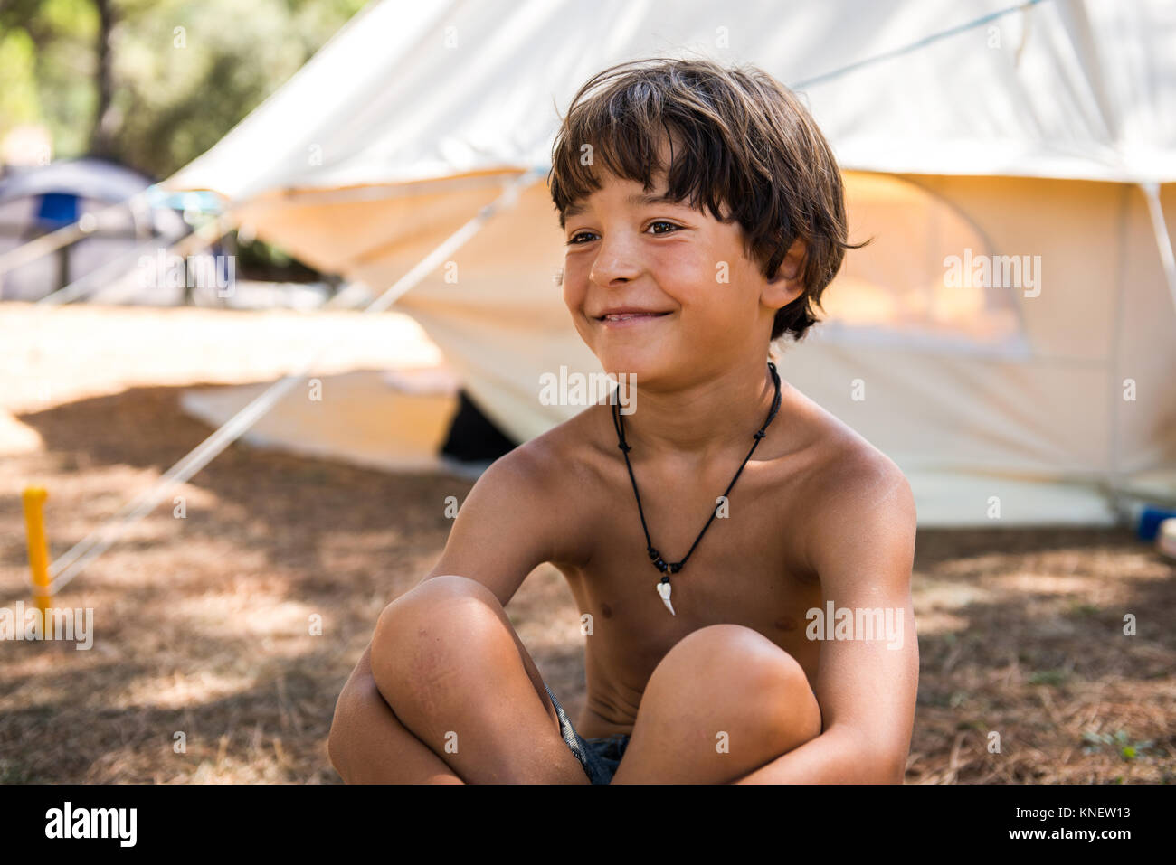Happy bare chested boy sitting on campsite - Stock Image
