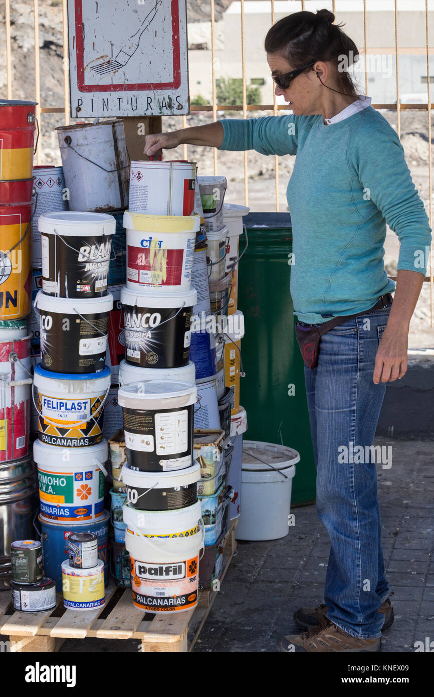 Spanish woman disposing of pain tins at council recycling centre in  Spain. - Stock Image