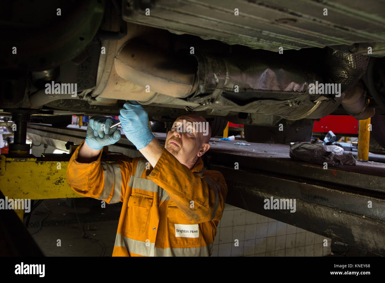 A mechanic working on the engine of a bus from underneath, at the Brighton and Hove Bus Depot - Stock Image