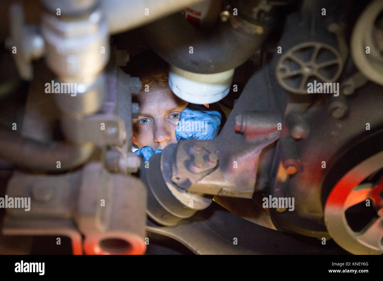 A mechanic working on the engine of a bus from underneath. - Stock Image