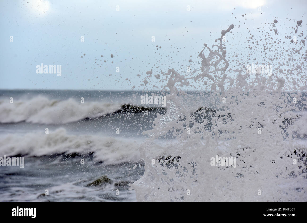 stormy seas and foaming waves smashing onto a sea wall and filling the air with spume and spray. Stormy winter weather - Stock Image