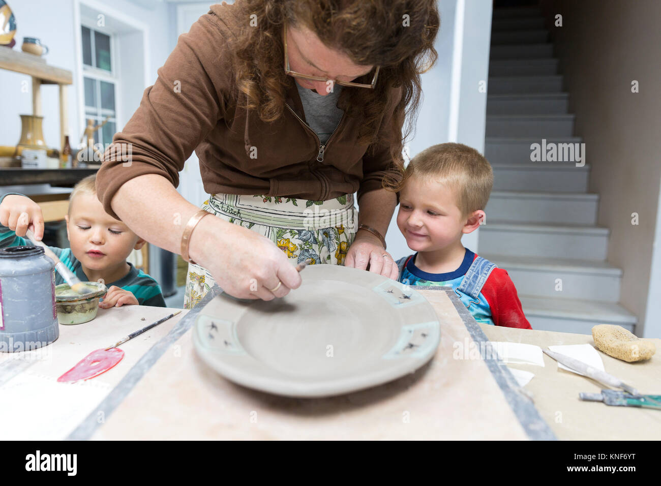 Potter painting platter watched by sons - Stock Image