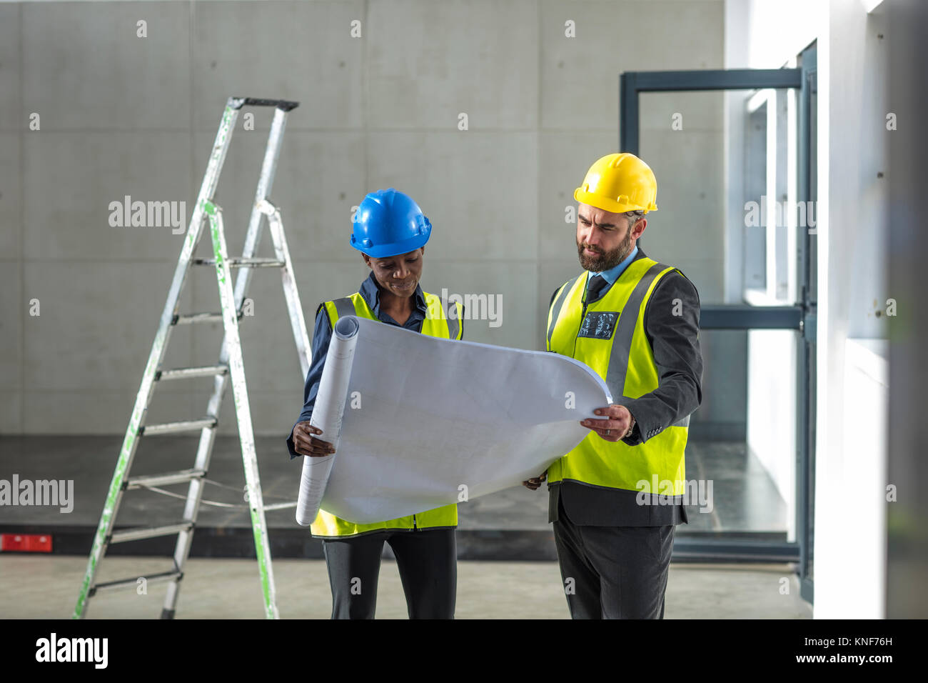 Colleagues with hard hat and hi viz jacket looking at blueprint Stock Photo