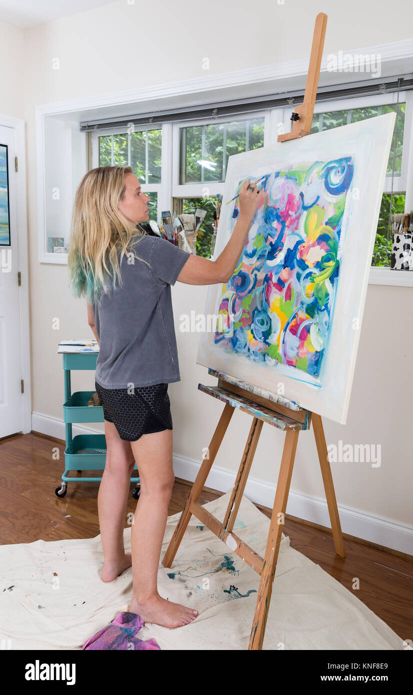 Female artist painting abstract canvas  in studio - Stock Image