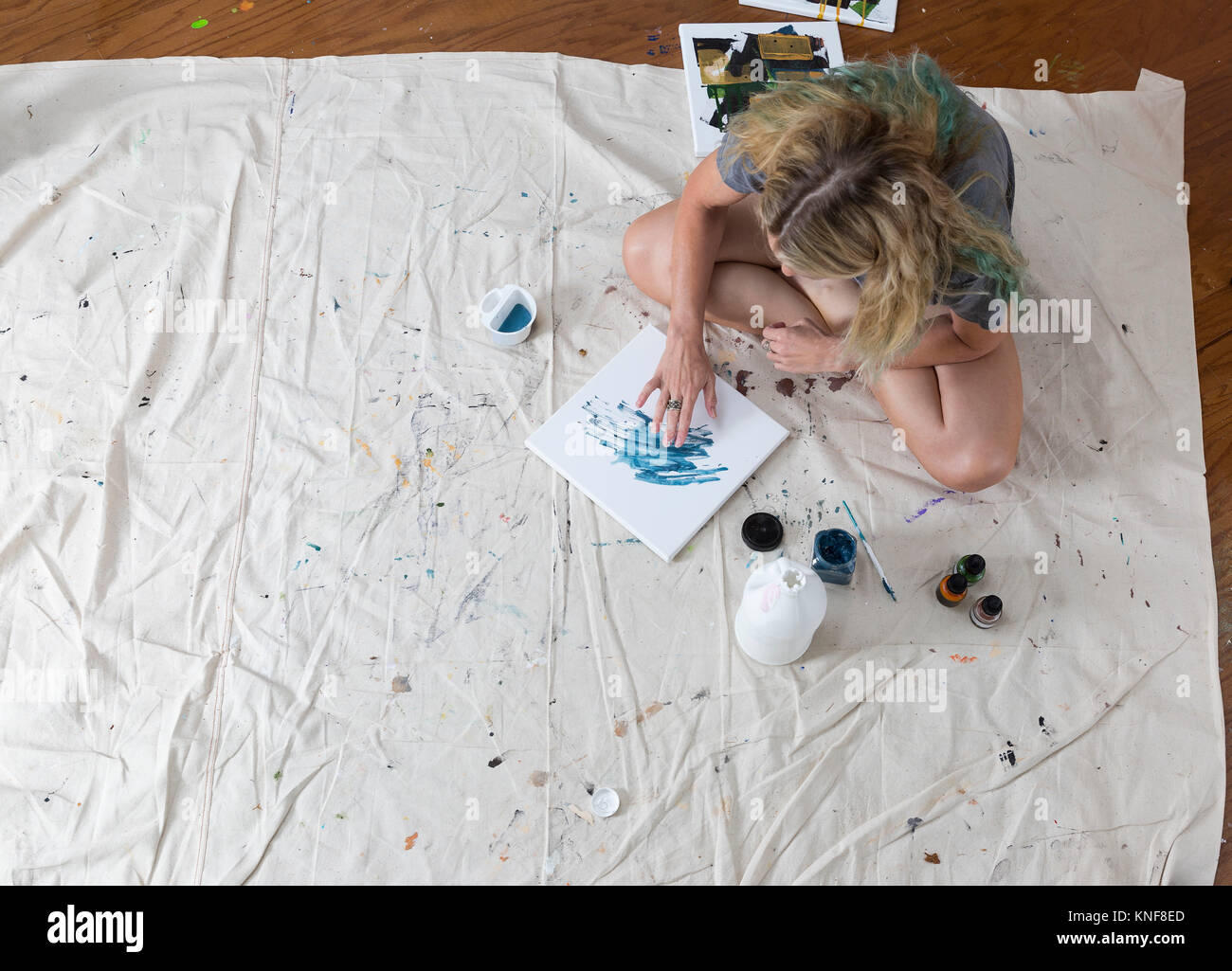 Overhead view of female artist sitting on dust sheet finger painting abstract canvas - Stock Image