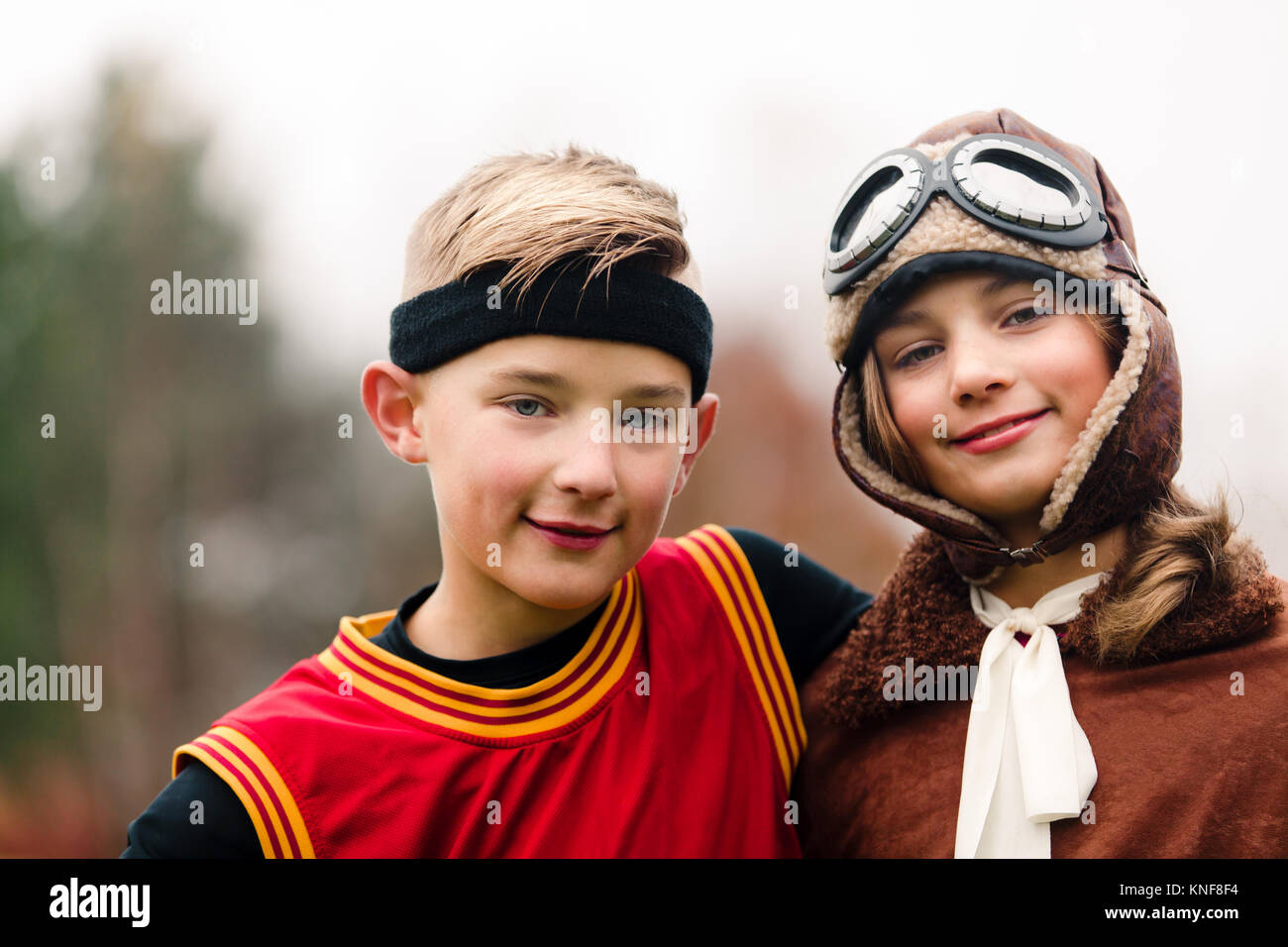 Portrait of boy and twin sister wearing basketball and pilot costumes for halloween - Stock Image
